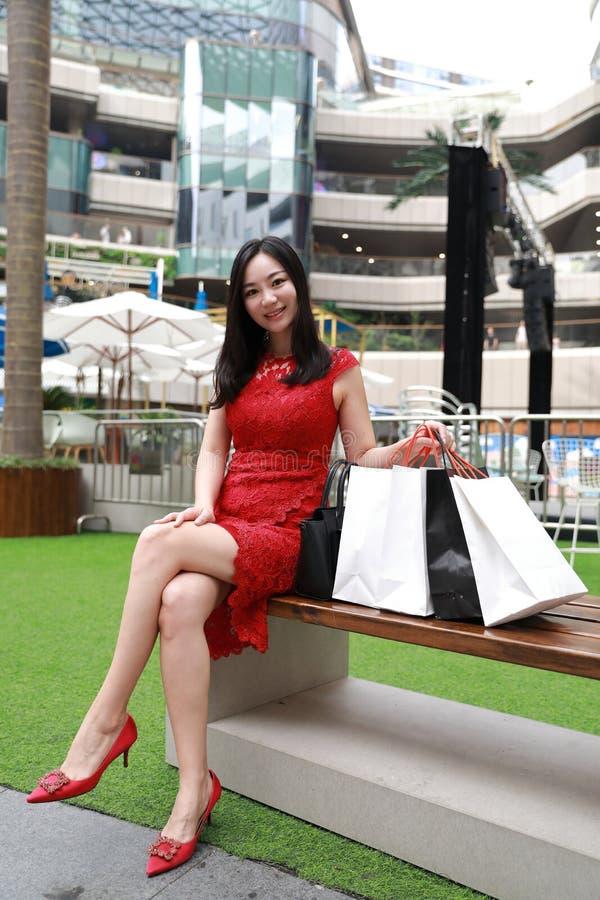 愉快的亚洲中国现代在高跟购物中心商店偶然买家微笑的笑的时髦的女人女孩腿购物的卡片袋子 库存图片