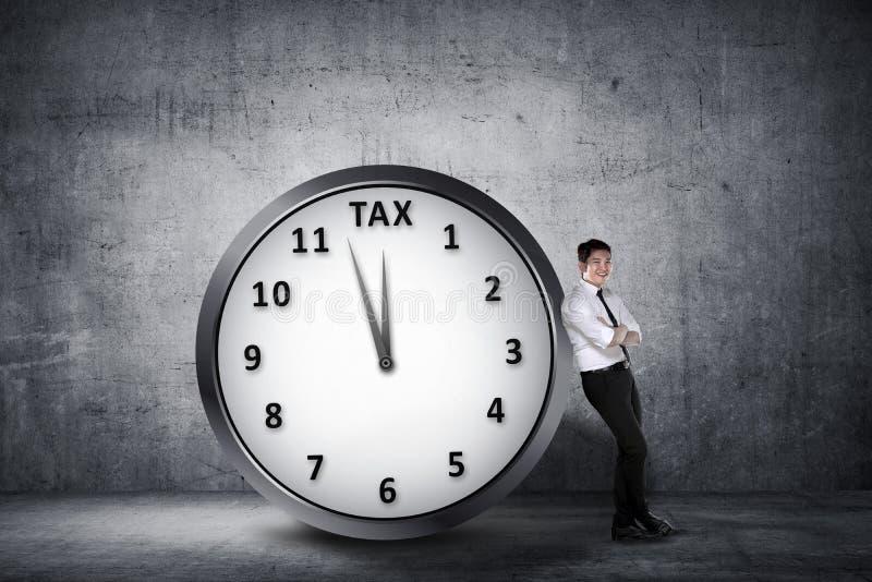 愉快的亚洲商人在有最后期限的蒂姆时钟倾斜  免版税库存图片