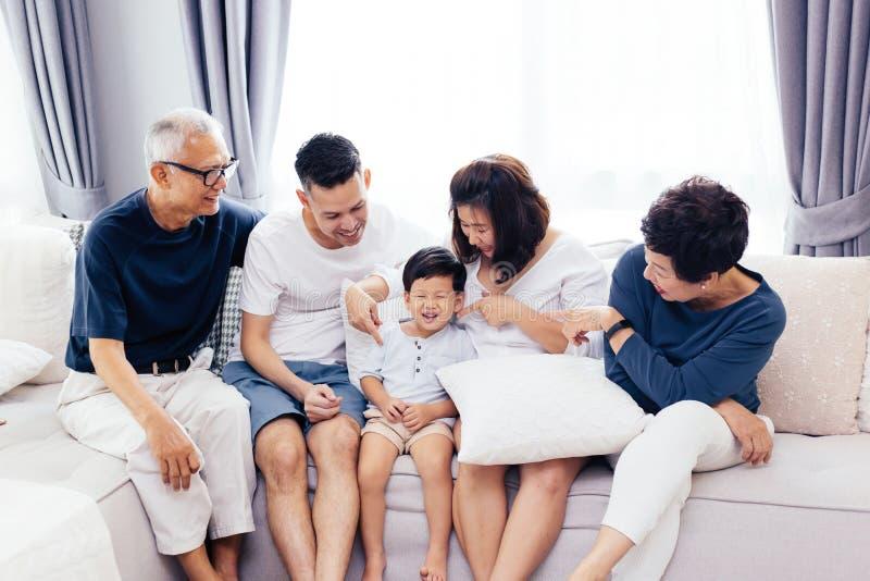 愉快的亚洲大家庭一起坐沙发,摆在为小组照片 图库摄影