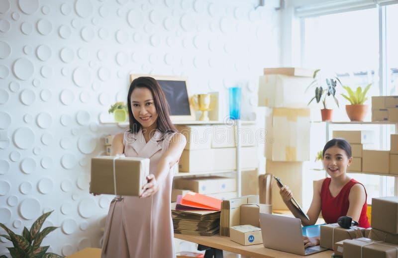 愉快的亚洲女商人所有者藏品小包和在网上,女性微笑的发动offic企业家的SME在家 库存照片