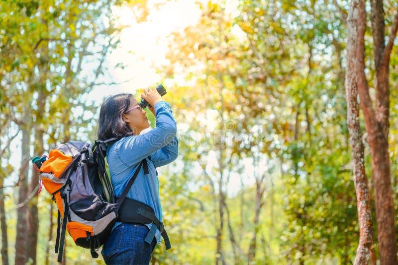 愉快的亚洲女孩背包在公园和森林背景中放松在假日概念旅行的时间 免版税库存图片