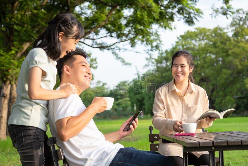 愉快的亚洲家庭、小孩女孩或者女儿在早晨一起享用,父亲谈话,乐趣,父母喝咖啡或茶,微笑 免版税库存照片