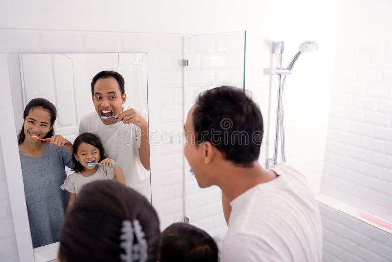愉快的亚洲家庭一起刷他们的牙 免版税库存图片