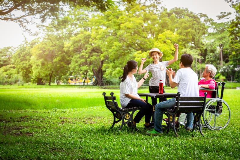 愉快的亚洲家庭在室外公园,父亲、母亲有小孩女孩的或女儿戏剧,跳舞,唱歌,获得年长的妇女乐趣, 免版税库存图片