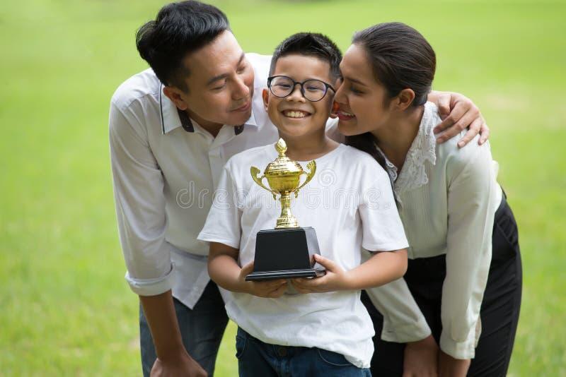 愉快的亚洲结合在一起使战利品的家庭、父母和他们的孩子在公园 父母拥抱和亲吻儿子 库存图片