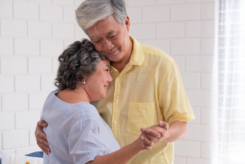 愉快的亚洲资深夫妇在客厅享受缓慢的跳舞在房子里激动温暖的爱 祖母偎依祖父 库存图片