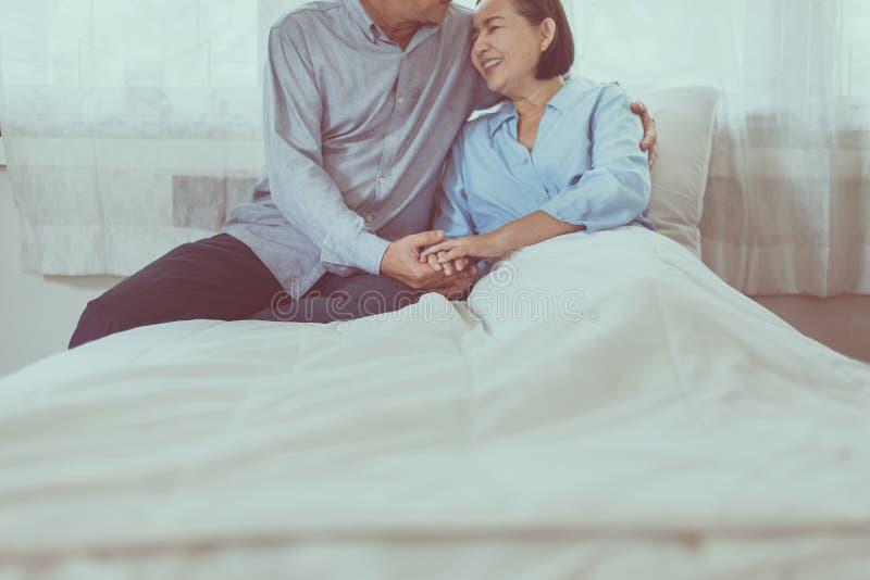 愉快的亚洲资深夫妇鼓励和一起拥抱在床上,愉快和微笑,正面认为 免版税库存图片