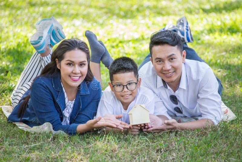 愉快的亚洲躺下在草的家庭、父母和他们的孩子在一起看照相机的公园 父亲、母亲和儿子 免版税库存图片