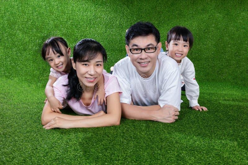 愉快的亚裔中国说谎在草的父母和女儿 免版税图库摄影