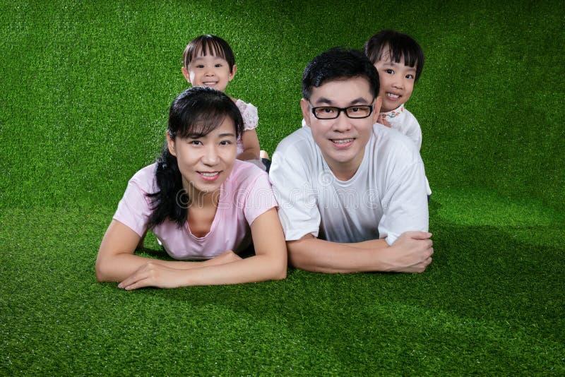 愉快的亚裔中国说谎在草的父母和女儿 库存图片