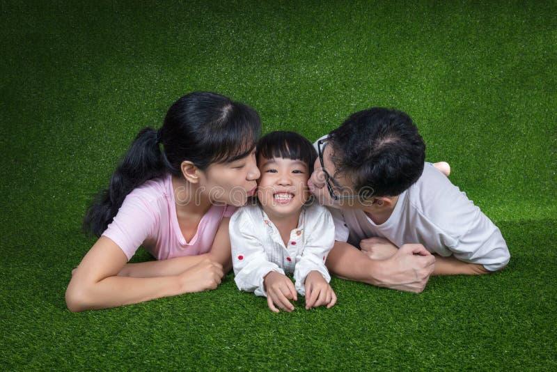 愉快的亚裔中国说谎在草的父母和女儿 免版税库存图片