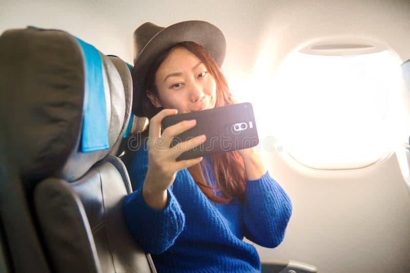 愉快的亚裔乘客坐飞机在窗口和作为附近在您的智能手机的一selfie 免版税库存图片