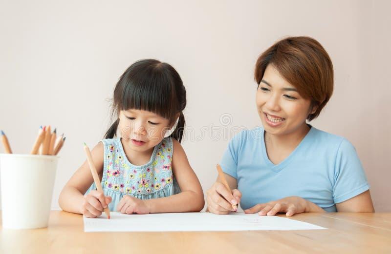 愉快的亚裔使一致母亲和的女儿 免版税库存图片