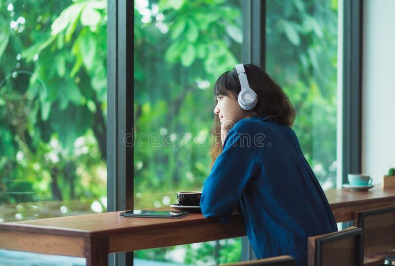 愉快的亚裔偶然与耳机的妇女听的音乐临近wi 库存图片