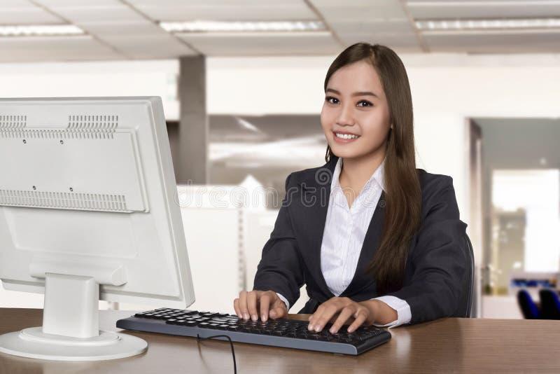 愉快的亚裔女商人与一台台式计算机一起使用 免版税库存照片