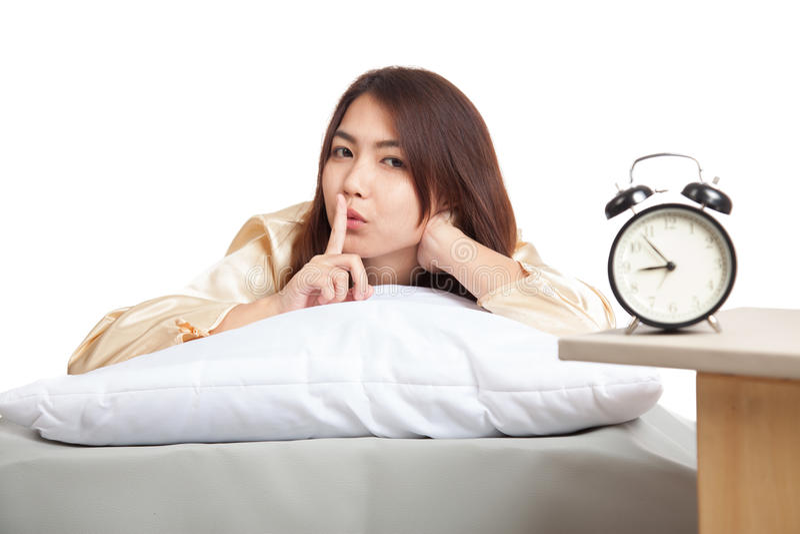 愉快的亚裔女孩叫醒与闹钟的展示安静的标志 免版税图库摄影