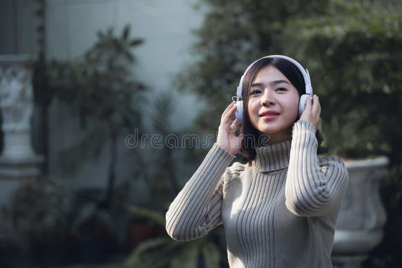 愉快的亚裔女孩听到音乐 免版税库存照片