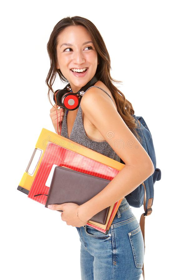 愉快的亚裔女生的边反对被隔绝的白色背景的与袋子和书 库存照片