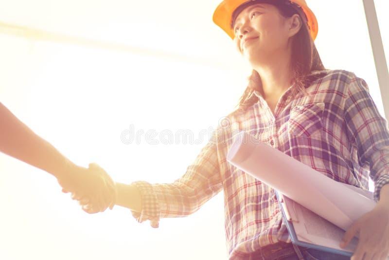 愉快的亚裔妇女工程师当有图纸的建筑工人 免版税库存图片