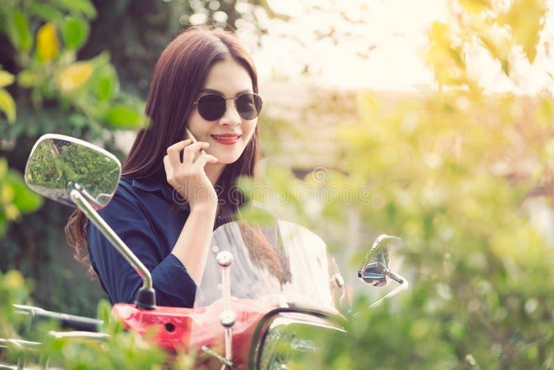 年轻愉快的亚裔妇女谈话在她的电话在她的红色motorcyc 免版税库存图片