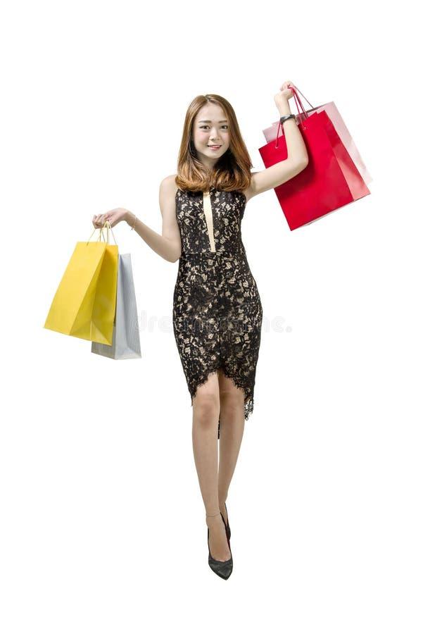 愉快的亚裔妇女运载的购物袋摆在 库存图片