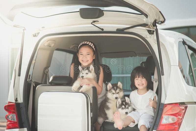愉快的亚裔孩子和西伯利亚爱斯基摩人小狗开会 免版税库存照片