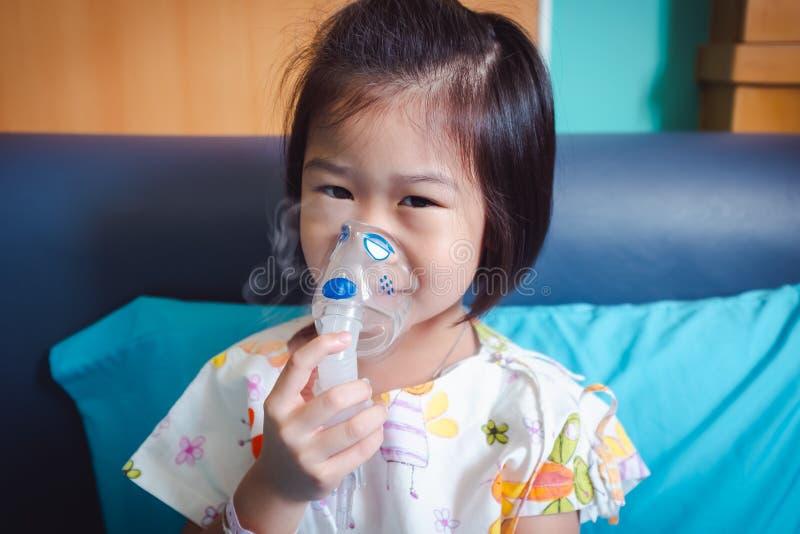 愉快的亚裔孩子拿着哮喘的治疗的一台面具蒸气吸入器 免版税库存照片