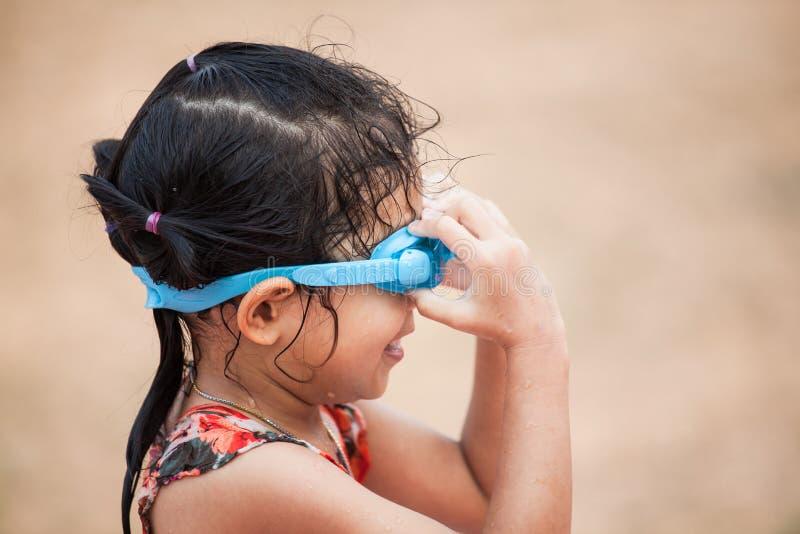愉快的亚裔小孩女孩佩带的游泳风镜 免版税库存照片