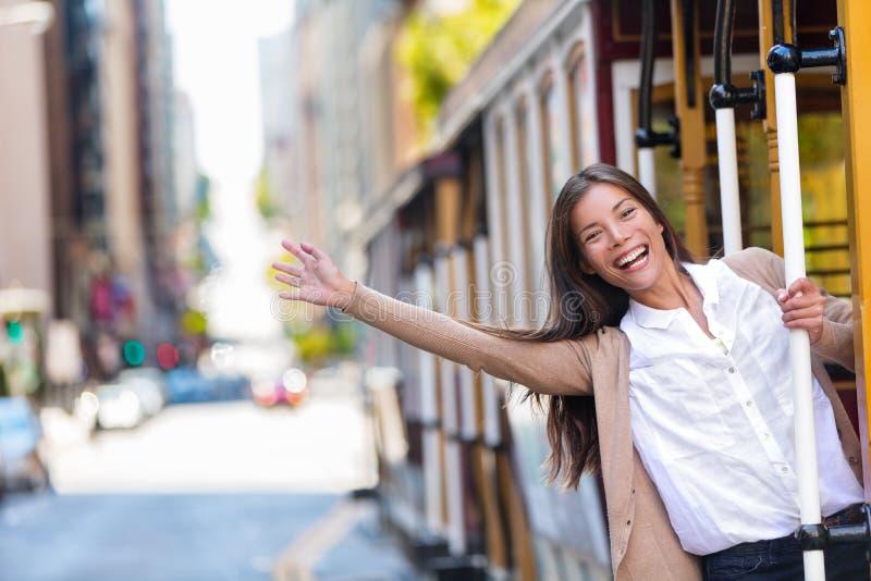 愉快的亚裔年轻女人激动获得乘坐普遍的旅游景点电车轨道电车系统的乐趣在旧金山市, 免版税库存照片