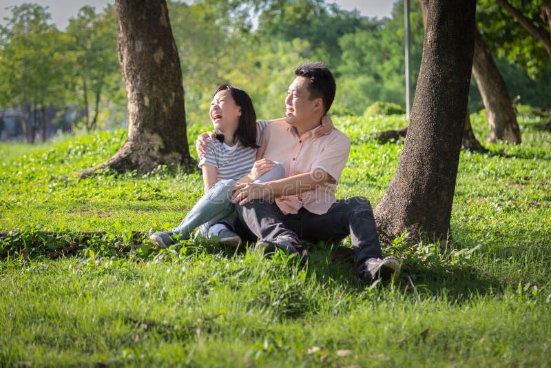 愉快的亚裔成人人和逗人喜爱的儿童女孩充满爱,拥抱和微笑在夏天自然、父亲和一点美丽的女儿 图库摄影