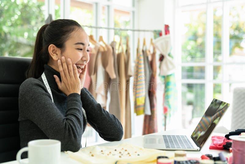 愉快的亚裔时装设计师激动,微笑,看好消息,通知,销售订单,在膝上型计算机的成交的惊奇在现代办公室 免版税图库摄影