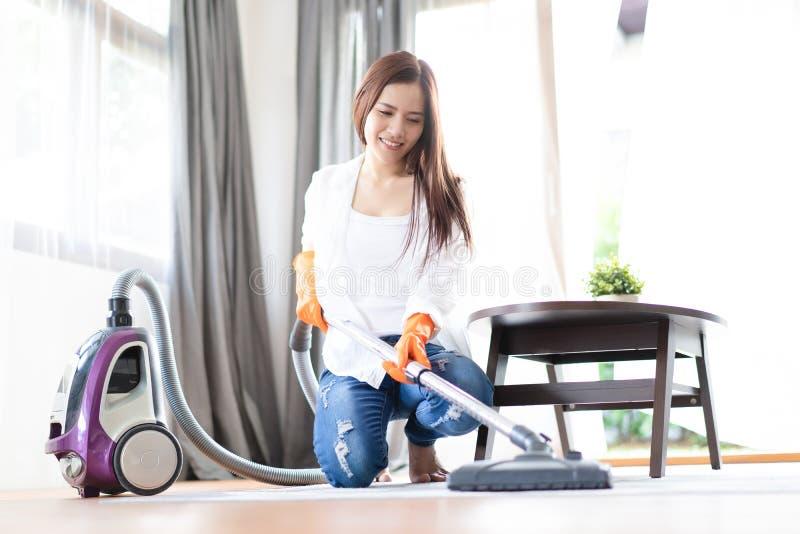 愉快的亚裔有吸尘器的妇女清洗的地毯在客厅 家事、cleanig和差事概念 库存图片