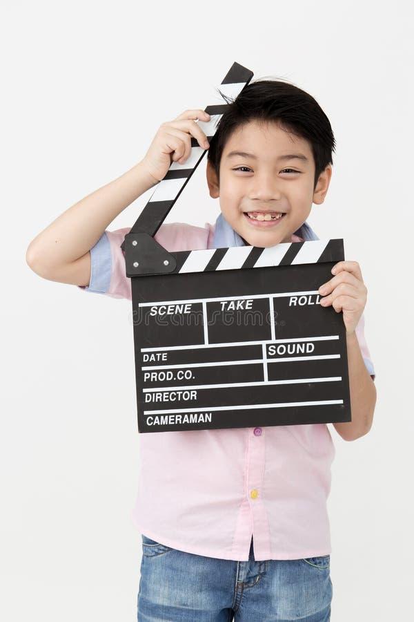 愉快的亚裔男孩在手上的拿着拍板 戏院概念 库存图片