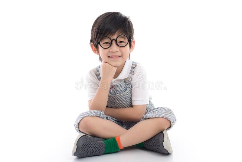 愉快的亚裔男孩坐白色背景 免版税库存照片