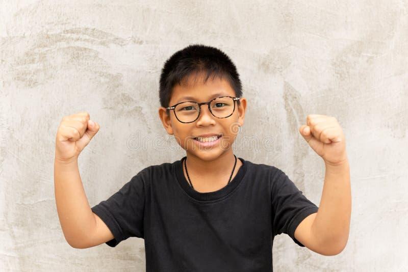 愉快的亚裔男孩用玻璃手和微笑在灰色背景 免版税库存照片
