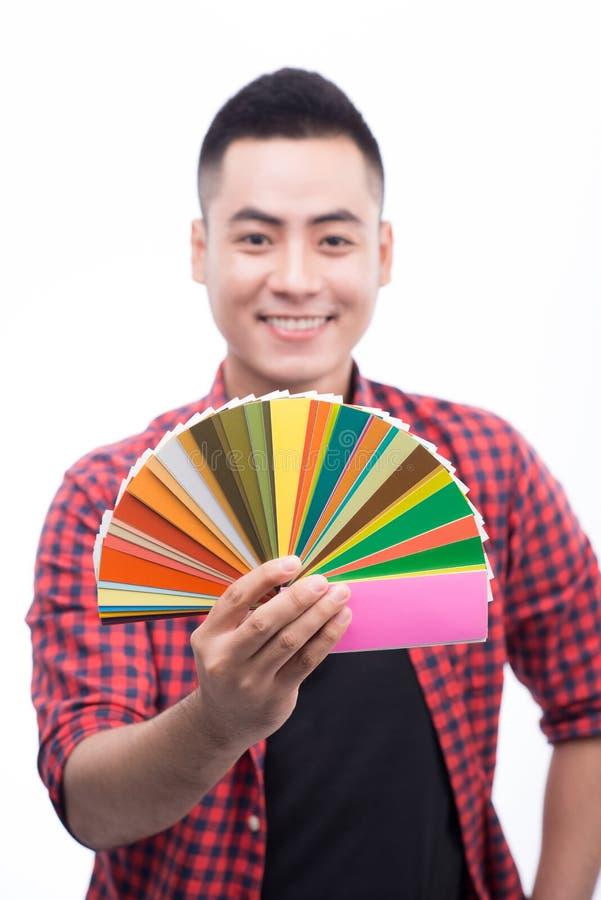 愉快的亚裔男性图表设计师在他的手上的拿着颜色爱好者 免版税库存图片