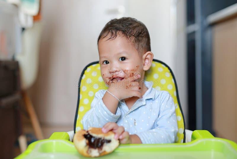 愉快的亚裔矮小的男婴坐孩子主持被弄脏室内吃的面包用被充塞的巧克力充满的点心和  免版税库存照片