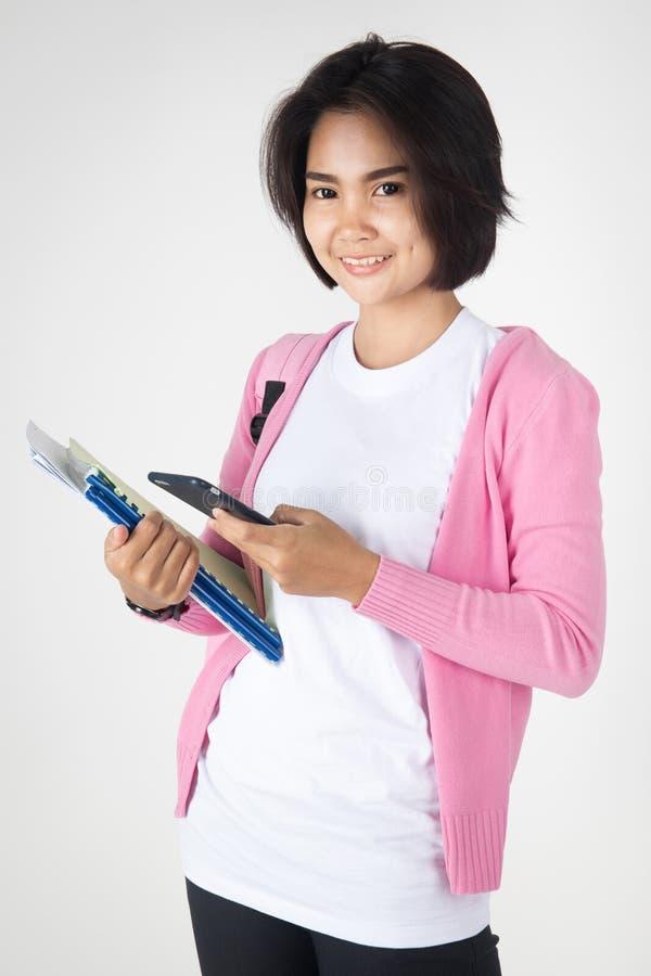 愉快的亚洲学生举行文具工具和手机 库存图片