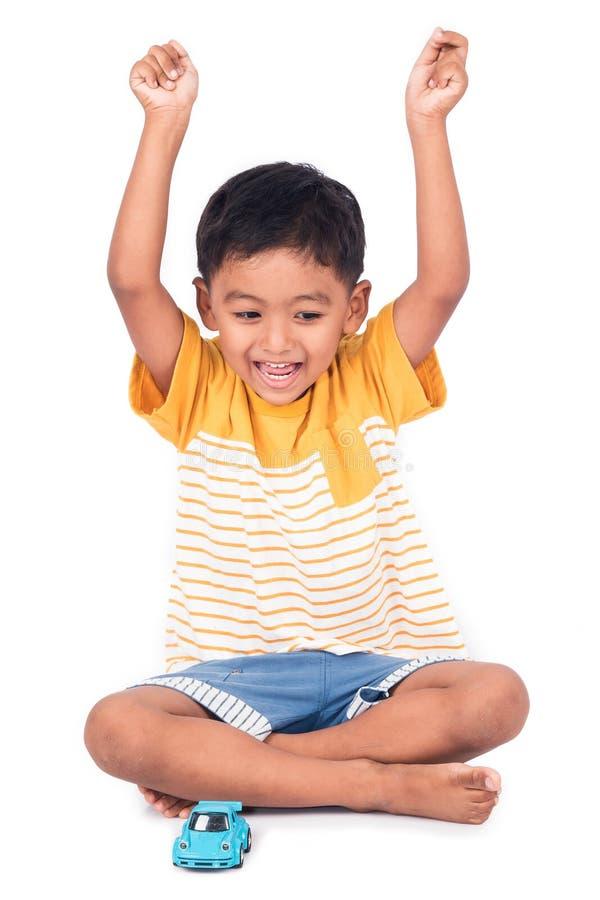 愉快的亚洲小男孩微笑和展示递成功 免版税库存图片