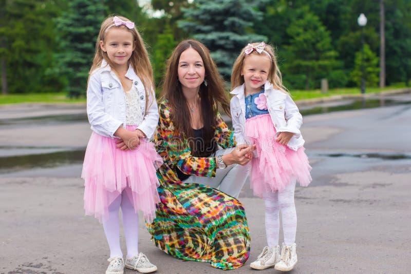 愉快的享受温暖的天的母亲和可爱的女孩 免版税库存图片