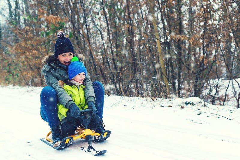 愉快的享受雪橇乘驾的母亲和她的儿子 与雪撬的愉快的家庭在获得的冬天乐趣一起 儿童sledding 家庭drivin 免版税图库摄影