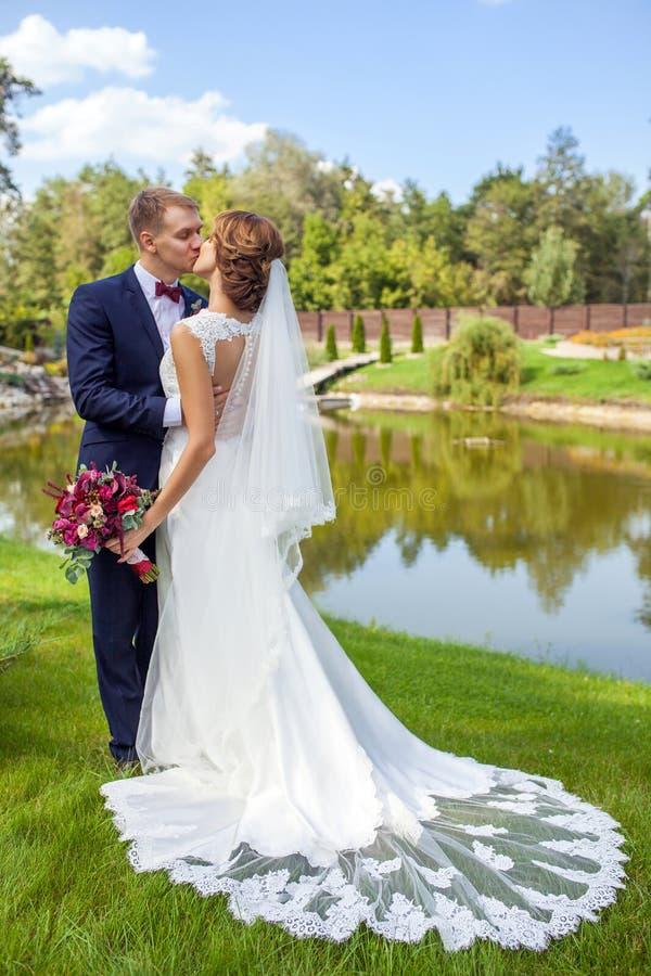愉快的亲吻新郎和的新娘,当站立在绿草近时 免版税图库摄影