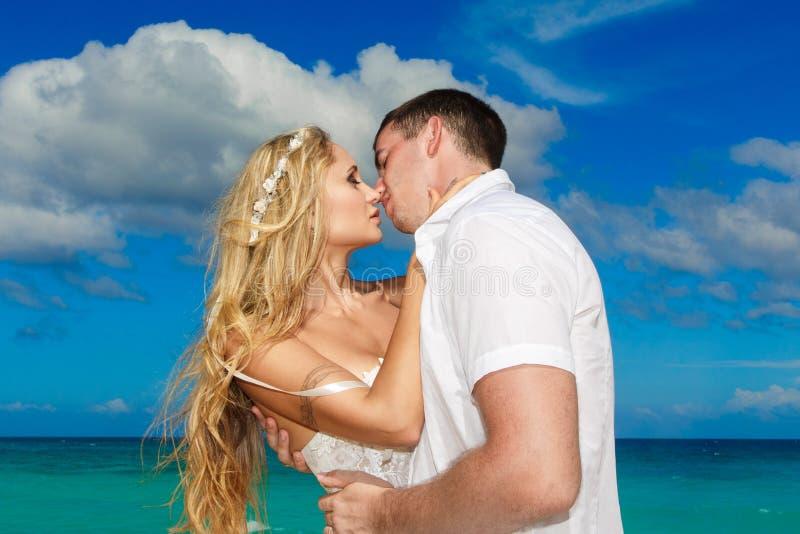 愉快的亲吻在一个热带海滩的新娘和新郎 t的蓝色海 图库摄影