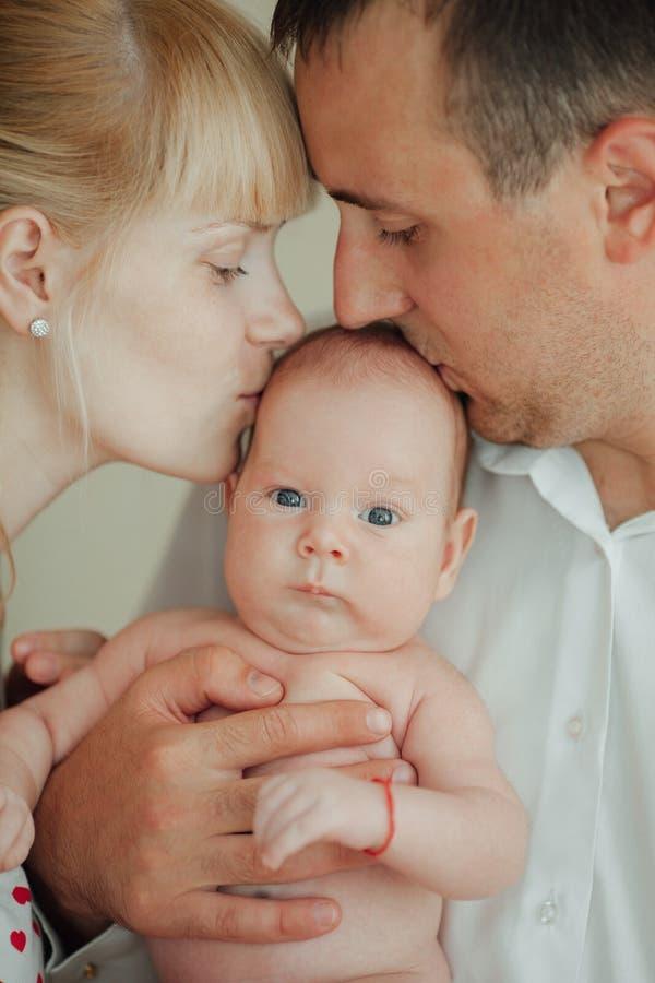 愉快的亲吻婴孩的母亲和父亲 免版税图库摄影