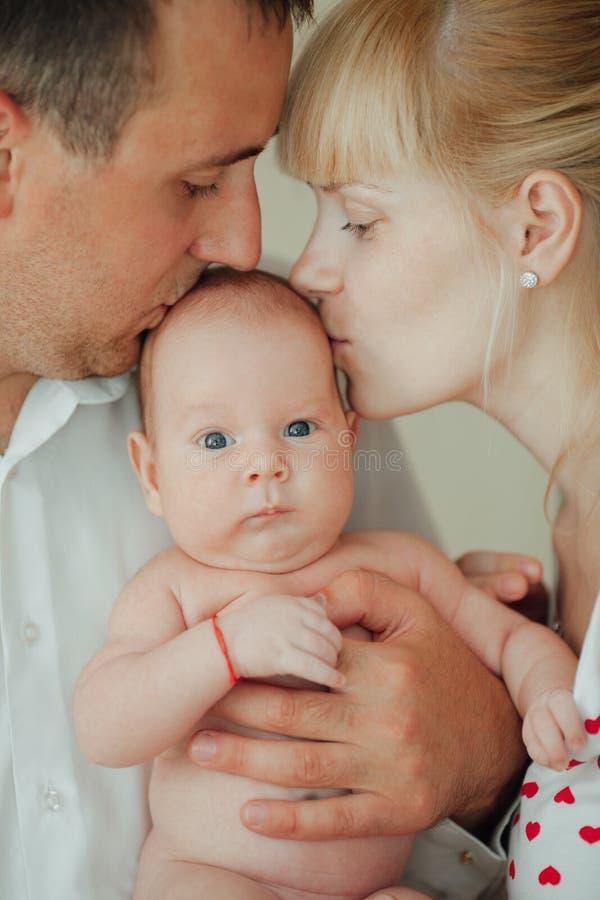 愉快的亲吻婴孩的母亲和父亲 库存照片