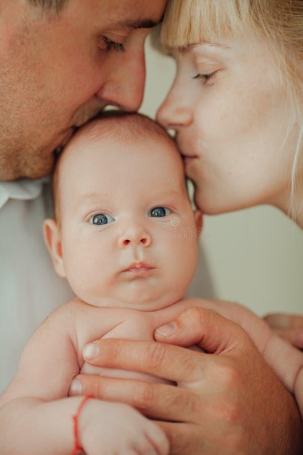 愉快的亲吻婴孩的母亲和父亲 库存图片