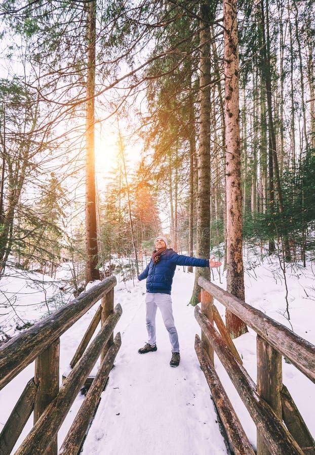 愉快的人享用与冬天步行在森林里 免版税库存照片