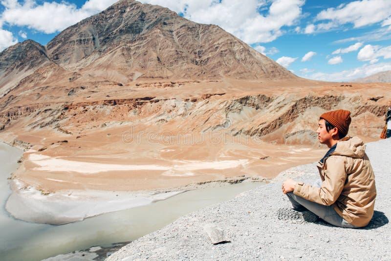 年轻愉快的人坐在旅行的峭壁在印度河在Leh,拉达克,印度 免版税库存图片