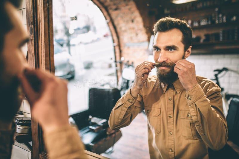 愉快的人接触他的髭用两只手 他为它感到骄傲 库存图片