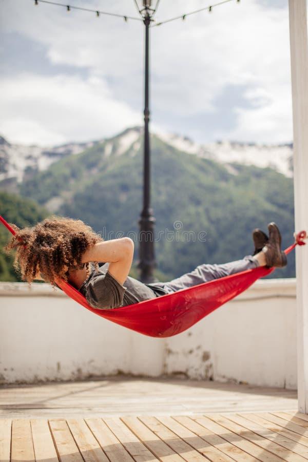 愉快的人放松的在在山顶部的吊床 暑假旅行生活方式概念 免版税图库摄影